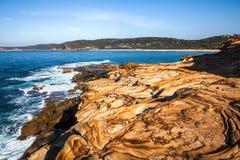 Ο όμορφος χρωματισμένος ψαμμίτης λικνίζει κοντά Putty στην παραλία, εθνικό πάρκο Bouddi, Αυστραλία στοκ φωτογραφία