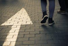 Οδός βελών κατευθείαν με τους περπατώντας ανθρώπους στο σκοτεινό τρύγο Στοκ Εικόνες