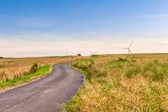 Οδός μέσω του λιβαδιού και σύγχρονοι ανεμοτροχοί για την οικολογική ενεργειακή παραγωγή στο υπόβαθρο Στοκ Φωτογραφία
