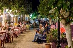 Οδός νύχτας με το σύνολο tavernas των τουριστών και οδός musicans στην πόλη Paleochora στο δυτικό μέρος του νησιού της Κρήτης Στοκ εικόνα με δικαίωμα ελεύθερης χρήσης