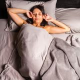 Ο ύπνος γυναικών στο κρεβάτι και τεντώνεται σε ένα σκοτεινό υπόβαθρο Στοκ φωτογραφίες με δικαίωμα ελεύθερης χρήσης