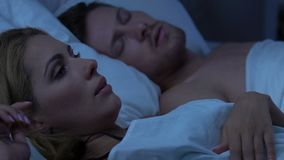 Ο ύπνος ζεύγους στο κρεβάτι, η σύζυγος από το δυνατό ροχαλητό που ξύπνησε του συζύγου απόθεμα βίντεο