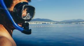 Ο δύτης νεαρών άνδρων με τη μάσκα για την κατάδυση και κολυμπά με αναπνευτήρα στο υπόβαθρο της θάλασσας με το διάστημα r Στοκ Φωτογραφία