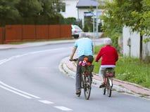Ο ώριμοι άνδρας και η γυναίκα οδηγούν ένα ποδήλατο μεταξύ των πρασίνων Ένα υγιές και ενεργό μέρος της ζωής Οικολογική μεταφορά γι Στοκ Φωτογραφία