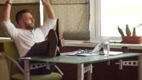 Ο ώριμος αρσενικός επιχειρηματίας στο άσπρο πουκάμισο ρίχνει τα πόδια του στον πίνακα Χρόνος ανάπαυλας, σπάσιμο στην εργασία, διά απόθεμα βίντεο