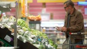 Ο ώριμος αρσενικός συνταξιούχος επιλέγει το λάχανο μπρόκολου στο φυτικό τμήμα μιας υπεραγοράς Τοποθέτηση των λαχανικών στο α απόθεμα βίντεο