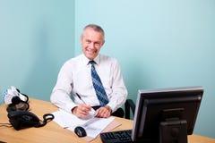Ο ώριμος επιχειρηματίας κάθισε στο γραφείο γραφείων του στοκ εικόνα