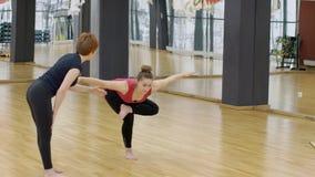 Ο ώριμος θηλυκός εκπαιδευτικός βοηθά τη νέα γυναίκα στην κατηγορία γιόγκας στη σύγχρονη γυμναστική, σε αργή κίνηση φιλμ μικρού μήκους