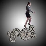 Ο busineswoman με cogwheels συνδέει στην έννοια ομαδικής εργασίας Στοκ Φωτογραφίες