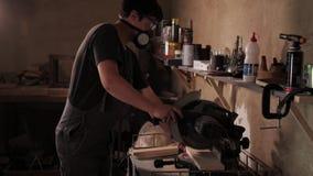 Ο craftman λειτουργεί στην ηλεκτρική μηχανή πριονιών Να πριονίσει έναν μεγάλο ξύλινο πίνακα απόθεμα βίντεο