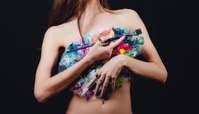 Ο Nude ελκυστικός νέος θηλυκός καλλιτέχνης κρατά μια παλέτα και μια βούρτσα χρώματος, unrecognizable Μαύρο υπόβαθρο στούντιο Στοκ Φωτογραφία