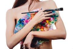 Ο Nude ελκυστικός νέος θηλυκός καλλιτέχνης κρατά μια παλέτα και μια βούρτσα χρώματος, εξετάζοντας τη κάμερα Άσπρο υπόβαθρο στούντ Στοκ εικόνες με δικαίωμα ελεύθερης χρήσης