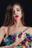 Ο Nude ελκυστικός νέος θηλυκός καλλιτέχνης κρατά μια παλέτα και μια βούρτσα χρώματος, εξετάζοντας τη κάμερα Μαύρο υπόβαθρο στούντ Στοκ Εικόνα
