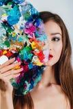 Ο Nude ελκυστικός νέος θηλυκός καλλιτέχνης κρατά μια παλέτα και μια βούρτσα χρώματος, εξετάζοντας τη κάμερα Άσπρο υπόβαθρο στούντ Στοκ Εικόνα