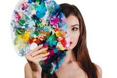Ο Nude ελκυστικός νέος θηλυκός καλλιτέχνης κρατά μια παλέτα και μια βούρτσα χρώματος, εξετάζοντας τη κάμερα Άσπρο υπόβαθρο στούντ Στοκ Φωτογραφία