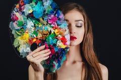 Ο Nude ελκυστικός νέος θηλυκός καλλιτέχνης κρατά μια παλέτα χρώματος και μια βούρτσα, ιδιαίτερες προσοχές Μαύρο υπόβαθρο στούντιο Στοκ Εικόνα