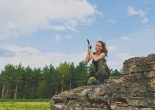 Ο Redhead στρατιώτης κοριτσιών είναι σε ένα γόνατο κρατώντας το πυροβόλο όπλο Στοκ εικόνα με δικαίωμα ελεύθερης χρήσης
