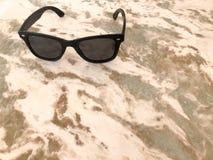 Ο Terry ήλιος-που ψήνουν τα πλαστικά γυαλιά με το μαύρο γυαλί και τα τόξα βρίσκονται σε μια καθαρή καφετιά άμμος-χρωματισμένη ελα Στοκ Εικόνες