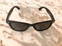 Ο Terry ήλιος-που ψήνουν τα πλαστικά γυαλιά με το μαύρο γυαλί και τα τόξα βρίσκονται σε μια καφετιά άμμος-χρωματισμένη ελαφριά πέ στοκ φωτογραφία με δικαίωμα ελεύθερης χρήσης