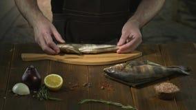 Ο Unrecognizable μάγειρας ή ο αρχιμάγειρας βάζει τα φρέσκα ψάρια στον τέμνοντα πίνακα για το αλάτισμα απόθεμα βίντεο