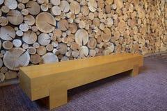 Πάγκος με τον τοίχο κούτσουρων Στοκ Φωτογραφίες