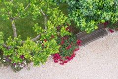 Πάγκος πάρκων με τα λουλούδια και την πορεία άνωθεν Στοκ εικόνα με δικαίωμα ελεύθερης χρήσης