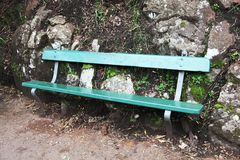 Πάγκος πάρκων σε πράσινο ενάντια σε έναν φυσικό τοίχο πετρών Στοκ φωτογραφία με δικαίωμα ελεύθερης χρήσης