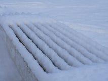 Πάγκος στην αλέα πάρκων που καλύπτεται με το χιόνι τον πρώιμο χειμώνα Στοκ Φωτογραφία