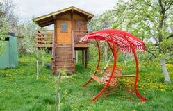 Πάγκος ταλάντευσης κοντά στο σπίτι παιδιών στον κήπο Στοκ εικόνες με δικαίωμα ελεύθερης χρήσης
