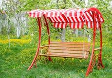 Πάγκος ταλάντευσης κοντά στο σπίτι παιδιών στον κήπο Στοκ Εικόνες