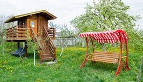Πάγκος ταλάντευσης κοντά στο σπίτι παιδιών στον κήπο Στοκ φωτογραφία με δικαίωμα ελεύθερης χρήσης