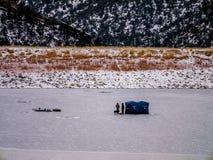 Πάγος ατόμων που αλιεύει στην παγωμένη λίμνη με το σκυλί Στοκ Εικόνες