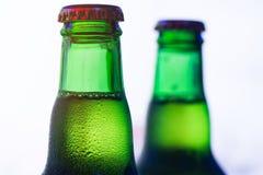 Πάγος - κρύο πράσινο μπουκάλι μπύρας στην άσπρη κινηματογράφηση σε πρώτο πλάνο υποβάθρου Στοκ Εικόνες