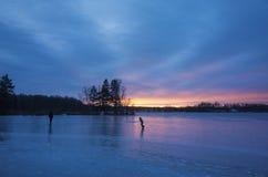 Πάγος πατέρων και γιων που κάνει πατινάζ στην παγωμένη λίμνη στο ηλιοβασίλεμα στοκ φωτογραφία
