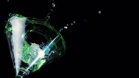 Πάγος που περιέρχεται στο γυαλί κοκτέιλ του πράσινου υγρού απόθεμα βίντεο