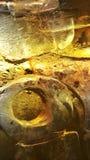 Πάγος στο γυαλί και τα πορτοκαλιά κίτρινα σταγονίδια μπύρας, αφηρημένο υπόβαθρο Στοκ Φωτογραφία
