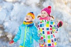 Πάλη σφαιρών χειμερινού χιονιού παιδιών Τα παιδιά παίζουν στο χιόνι Στοκ Εικόνα