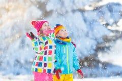 Πάλη σφαιρών χειμερινού χιονιού παιδιών Τα παιδιά παίζουν στο χιόνι στοκ φωτογραφίες
