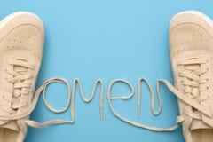 Πάνινα παπούτσια γυναικών με τις δαντέλλες στο κείμενο οιωνού στοκ φωτογραφία με δικαίωμα ελεύθερης χρήσης