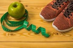 Πάνινα παπούτσια, εκατοστόμετρο και φρέσκια τοπ άποψη μήλων Υγιής και activ Στοκ Εικόνες