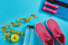 Πάνινα παπούτσια με τη μέτρηση της ταινίας στο κυανό μπλε υπόβαθρο Εκατοστόμετρο στο κίτρινο χρώμα, τα ρόδινα πάνινα παπούτσια, τ Στοκ εικόνα με δικαίωμα ελεύθερης χρήσης