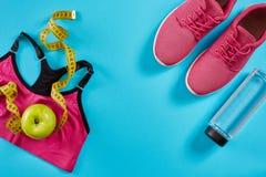 Πάνινα παπούτσια με τη μέτρηση της ταινίας στο κυανό μπλε υπόβαθρο Εκατοστόμετρο στο κίτρινο χρώμα, ρόδινα πάνινα παπούτσια, θηλυ Στοκ Εικόνες