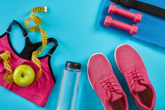 Πάνινα παπούτσια με τη μέτρηση της ταινίας στο κυανό μπλε υπόβαθρο Εκατοστόμετρο στο κίτρινο χρώμα, ρόδινα πάνινα παπούτσια, θηλυ Στοκ φωτογραφίες με δικαίωμα ελεύθερης χρήσης