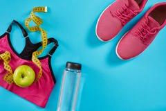 Πάνινα παπούτσια με τη μέτρηση της ταινίας στο κυανό μπλε υπόβαθρο Εκατοστόμετρο στο κίτρινο χρώμα, ρόδινα πάνινα παπούτσια, θηλυ Στοκ εικόνα με δικαίωμα ελεύθερης χρήσης
