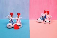 Πάνινα παπούτσια μωρών στο ρόδινο και μπλε υπόβαθρο, έννοια ντους μωρών Στοκ Εικόνα