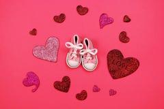 Πάνινα παπούτσια μωρών στο ρόδινο υπόβαθρο, έννοια ντους μωρών Στοκ Φωτογραφία