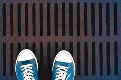 Πάνινα παπούτσια στον υπόνομο δικτυωτού πλέγματος υποβάθρου grunge για έναν περίπατο στην πόλη Στοκ Εικόνα