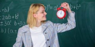 Πάντα εγκαίρως Ξυπνητήρι λαβής δασκάλων γυναικών Φροντίζει για την πειθαρχία χρόνος μελέτης Ευπρόσδεκτο σχολικό έτος δασκάλων στοκ φωτογραφία με δικαίωμα ελεύθερης χρήσης