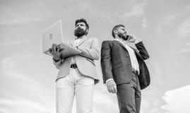 Πάντα στην αφή Ο καλλωπισμένος επιχειρηματίας ατόμων καλά κρατά ο συνεργάτης ότι lap-top μιλά το υπόβαθρο τηλεφωνικού μπλε ουρανο στοκ φωτογραφίες
