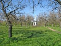 Πάρκο άνοιξη στον ηλιόλουστο καιρό με τις απόψεις του χριστιανικού παρεκκλησιού Στοκ Εικόνες